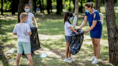 three children and one adult wearing masks in the woods cleaning up trash volunteering with children