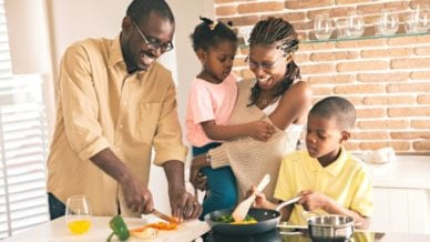 African American family cooking dinner together