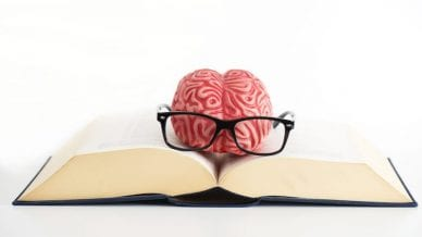 Brain with eyeglasses on top of a open book.