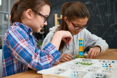 Girl students making tower from building blocks - STEAM Education Makes Our Students Better Risk-Takers. Here's Why.