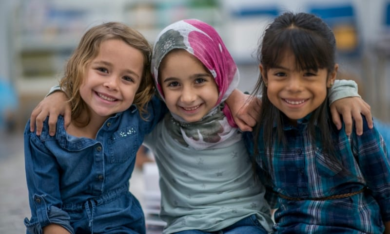 three young girls sit happily with their arms around one another