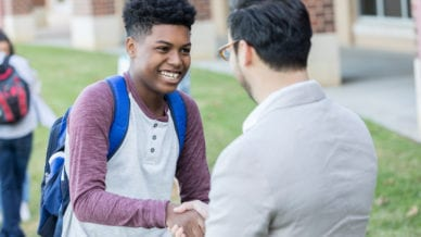 A teenage boy shakes hands with a High School teacher between classes outside his school building. He is receiving congratulations for a job well done.