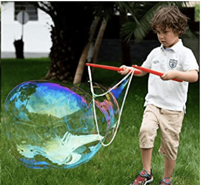 A boy playing with a giant bubble kit outside