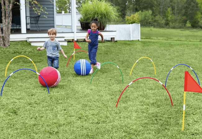 Two children playing a giant kick croquet game outside