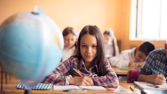 Young girl in classroom writing and looking at a globe – Simple Social Studies Activities That Incorporate Reading and Writing