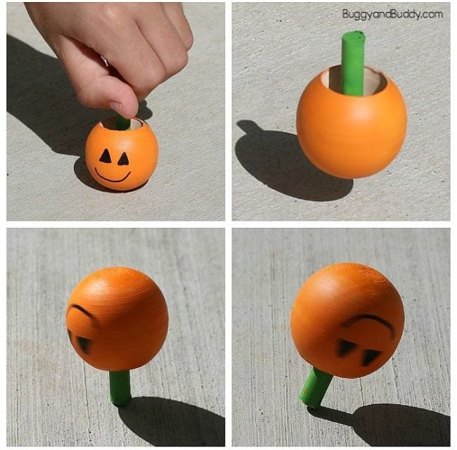 Inverted spinning wooden tops painted to look like a pumpkin (Halloween Activities)