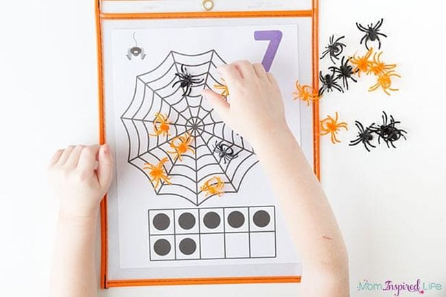 Student laying plastic spiders on a printable spiderweb 10 frame worksheet (Halloween Activities)
