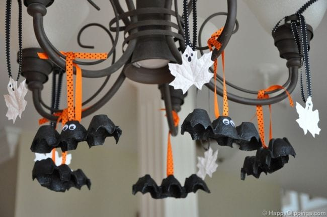 Leaves painted to look like ghosts and bats made of egg cartons hanging from a chandelier (Halloween Activities)
