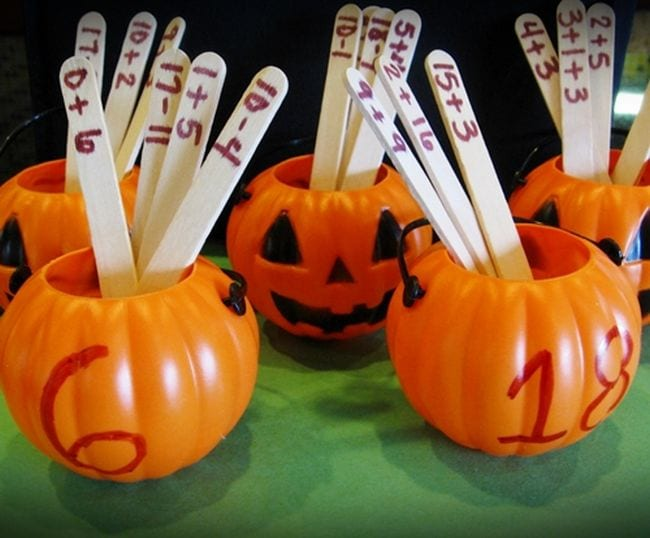 Small plastic pumpkins labeled with numbers filled with craft sticks with math problems written on them