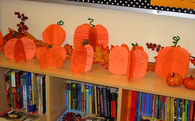 3-D paper pumpkins with stories written on them laid out on a bookshelf