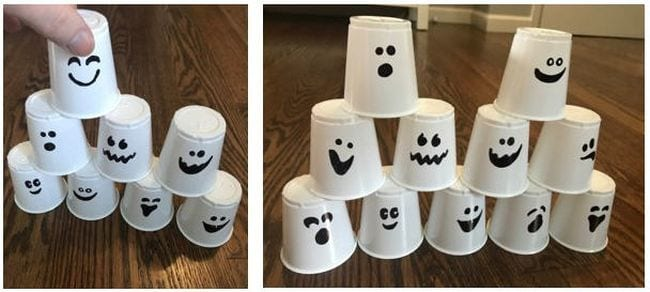 Student stacking white paper cups with ghost faces drawn on them (Halloween activities)
