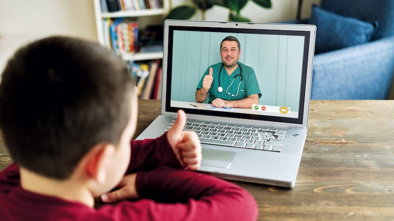 Cute child talking with doctor on video call. There is good news from doctor. Family is happy.