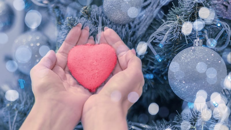 Female hands hold heart on Christmas tree.
