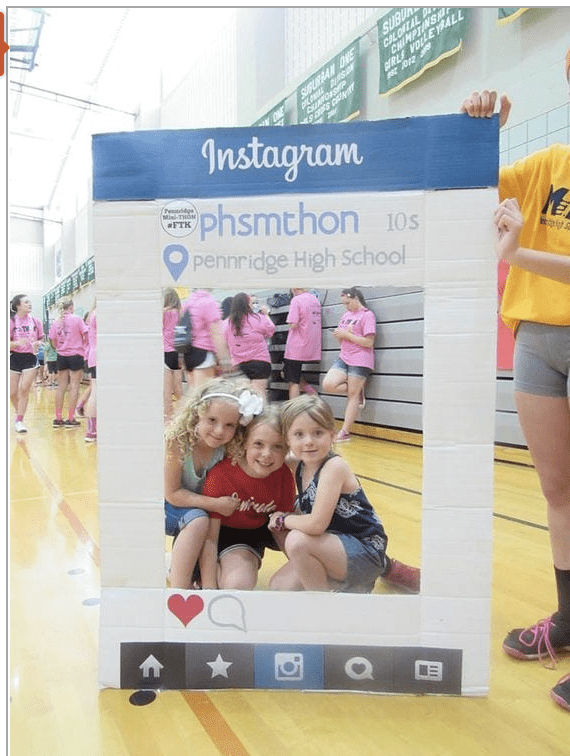 Three students in their school gym getting their photo taken in a photo booth.