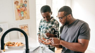 Black dad showing Black son how to count money teach kids about money