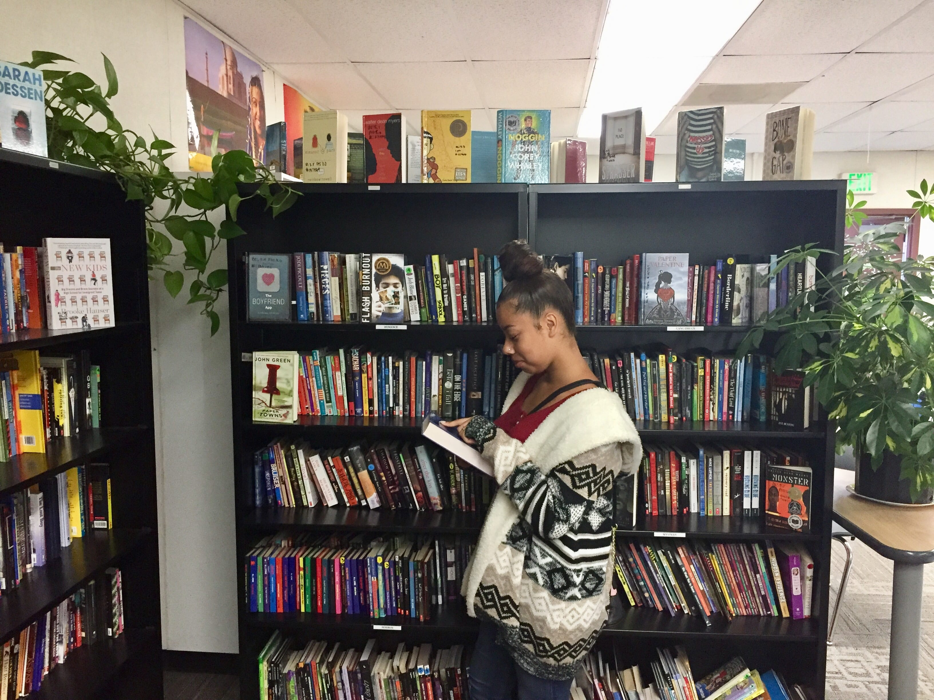 Student standing in front of bookshelves reading a book - help struggling readers