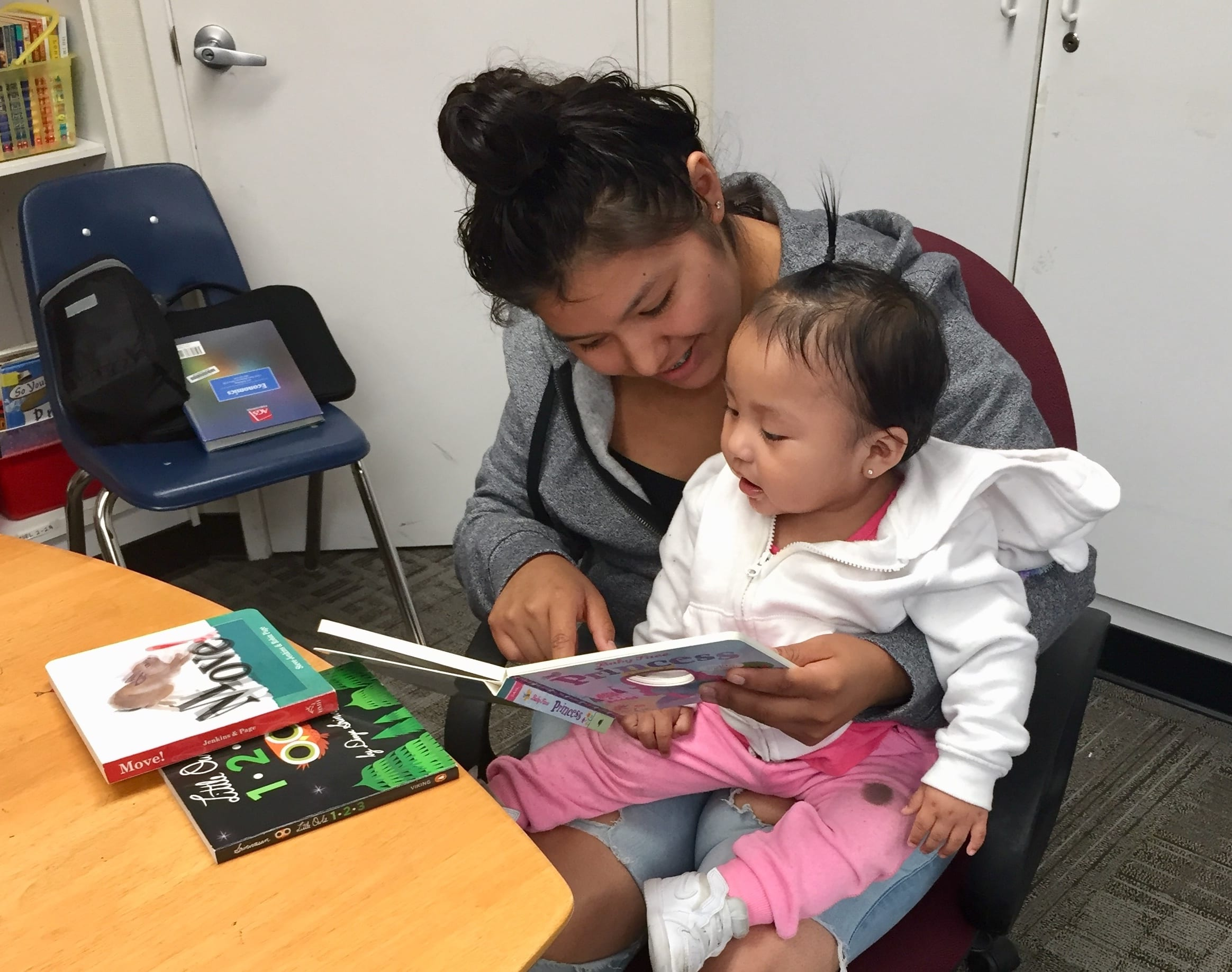 high school student reading to a baby