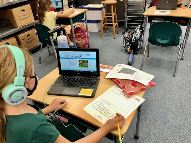 This student is researching the red fox on PebbleGo and writing down her findings.