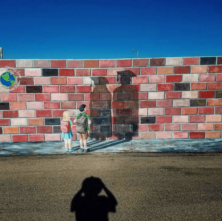 Imagine the future school mural with kids looking at their graduation shadows