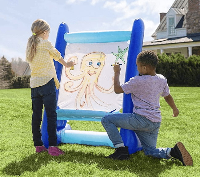 Two children outside painting on an inflatable easel, as an example of educational outdoor toys