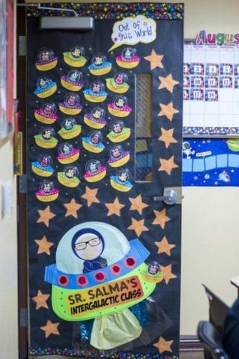 Classroom door decorated with teacher and students in small spaceships
