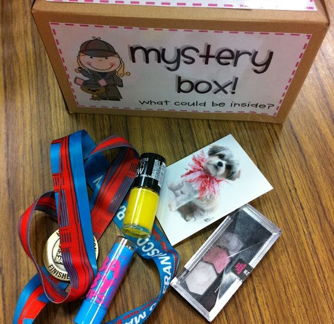 Cardboard box labeled Mystery Box with items like nail polish, photos, medal on a ribbon, and more