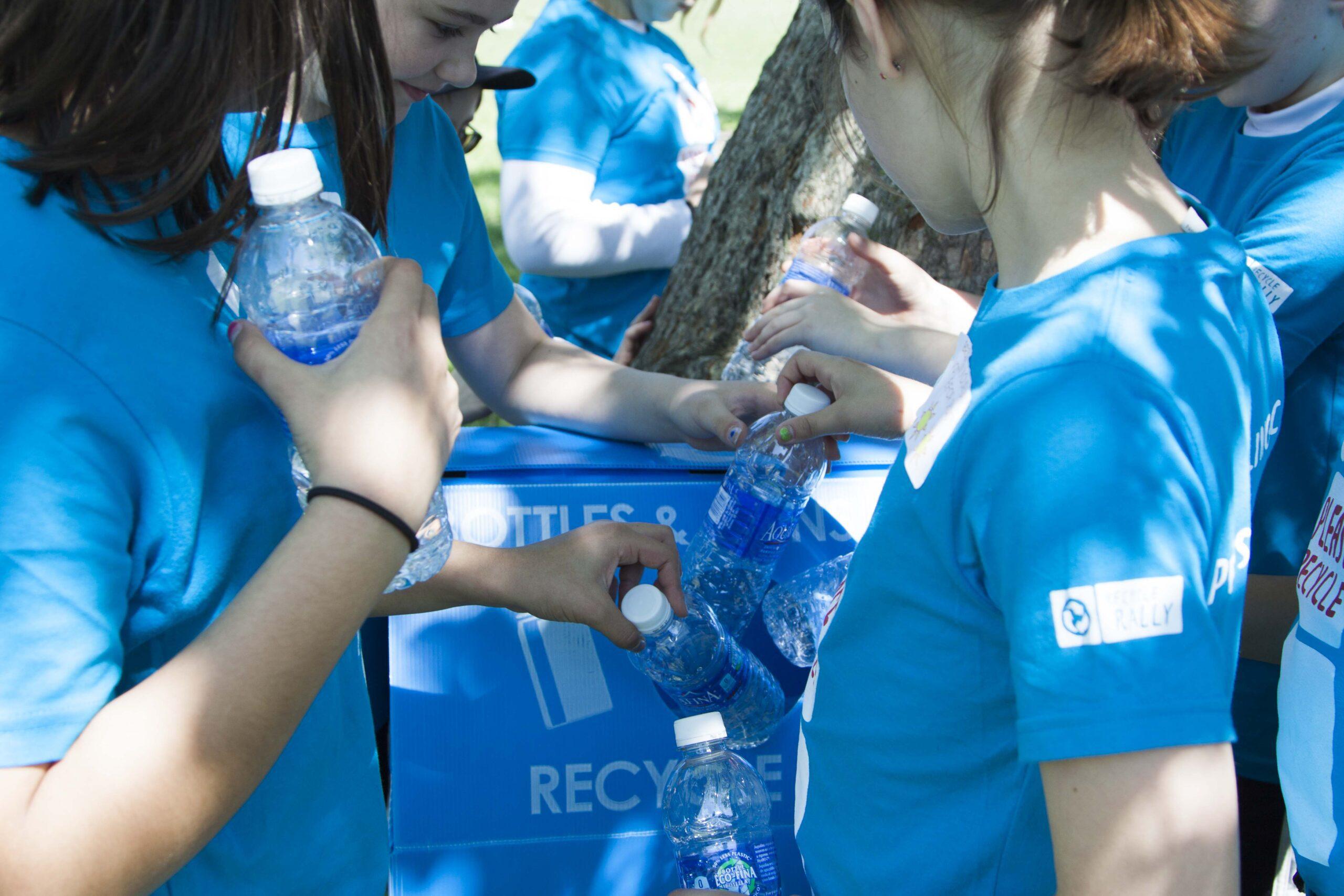 Kids recycling bottles in blue