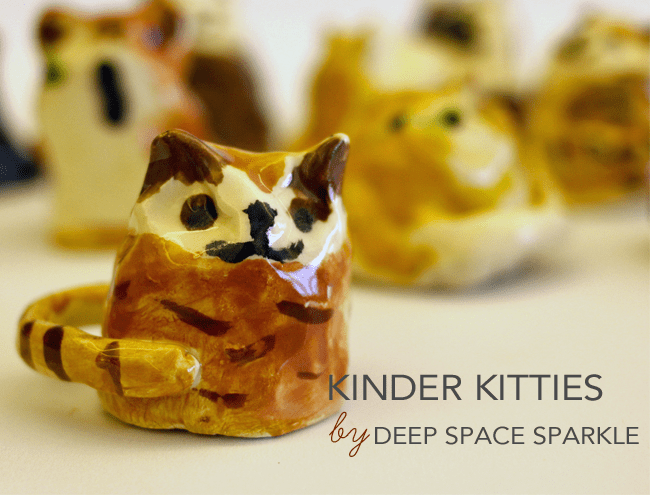 Simple clay cat figurines; text reads Kinder Kitties by Deep Space Sparkle