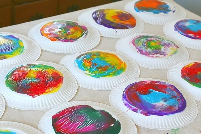 Paper plates painted with a variety of colorful designs
