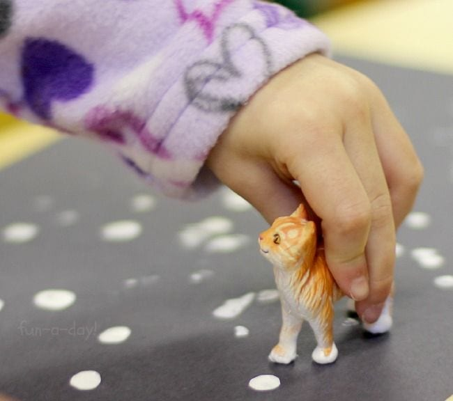 Child's hand holding a plastic cat figuring, using it to make paint white paw prints on a sheet of black paper