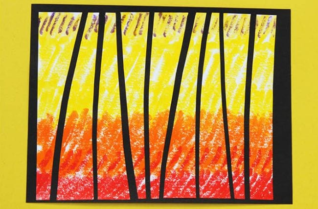 Red, orange, and yellow crayon design cut into pieces and glued on black paper