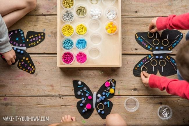 Young students adding beads, pom poms, and other embellishments to black paper butterflies