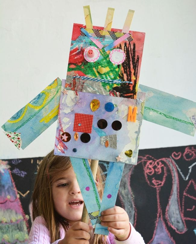 Kindergarten child holding a mixed media paper robot with buttons, fabric, and other materials (Kindergarten Art)