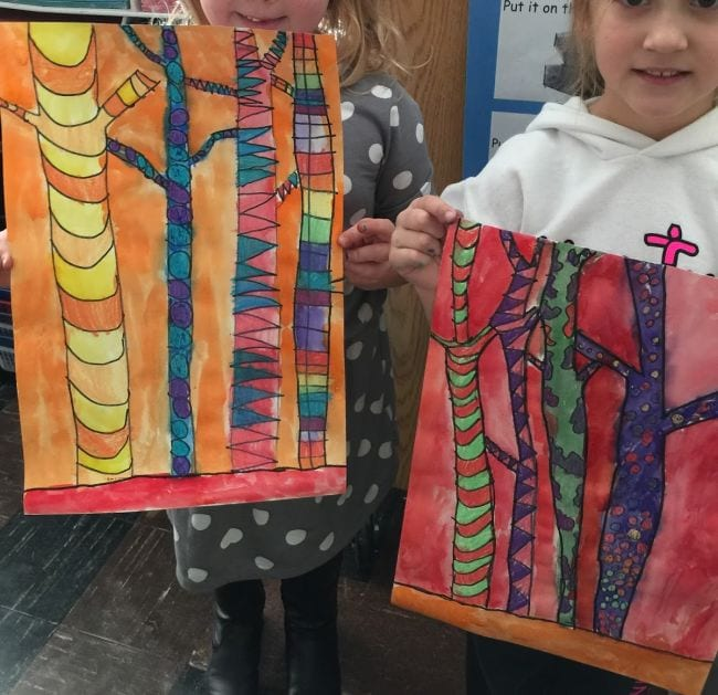 Children holding paintings of tree trunks, divided into sections with different colors and textures in each