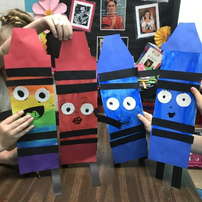 Students holding colorful oversized paper crayons with smiley faces (Kindergarten Art)