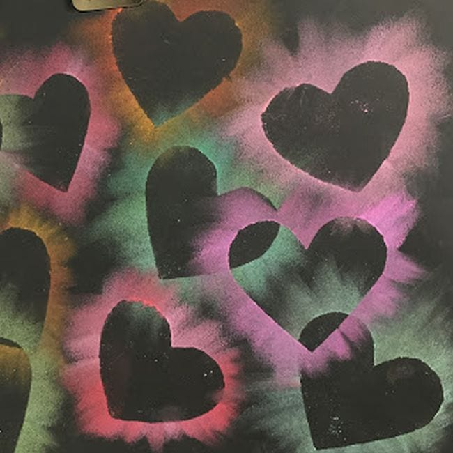 Black construction paper with heart shapes outlined by chalk pastels
