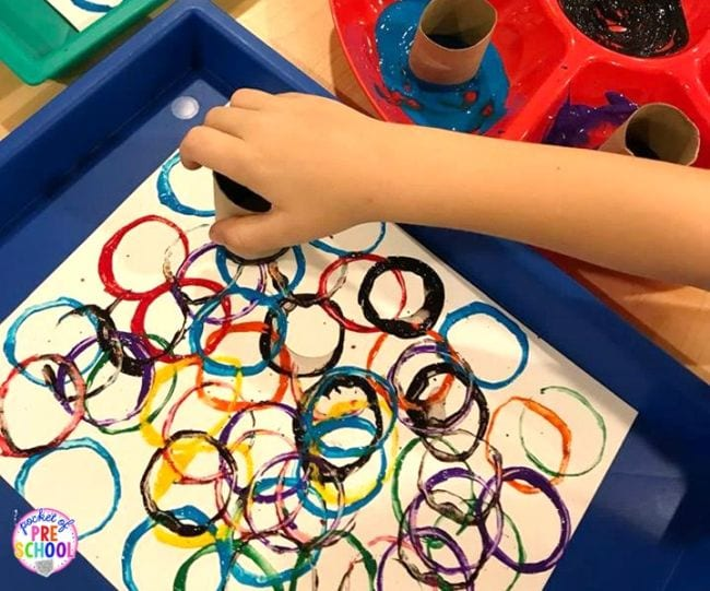 Kindergarten art student's hand using a toilet paper tube dipped in paint to make colorful circles