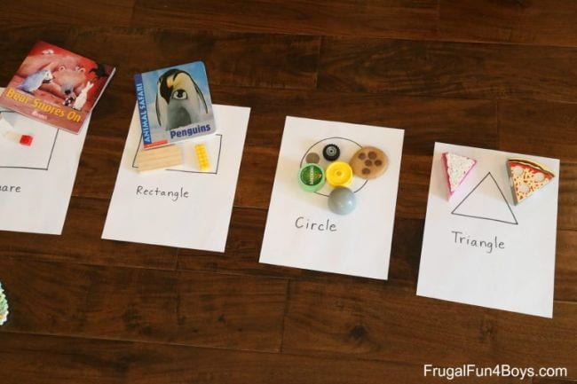 Papers labeled rectangle, circle, and triangle with various objects matching the shapes on each