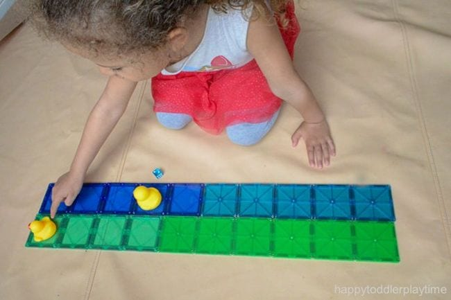 Kindergarten math student moving rubber ducks along a line of plastic tiles