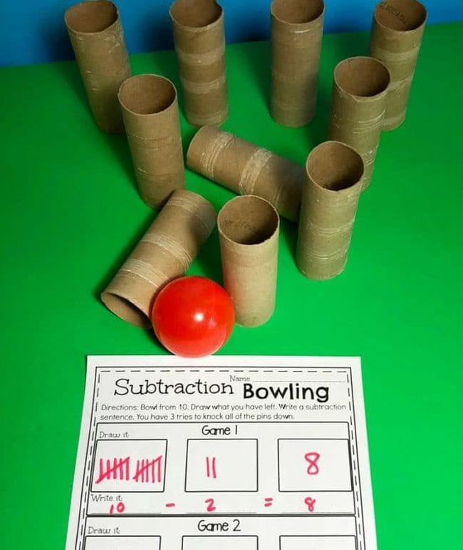 Toilet paper tubes set up like bowling pins, with a red ball and worksheet called Subtraction Bowling