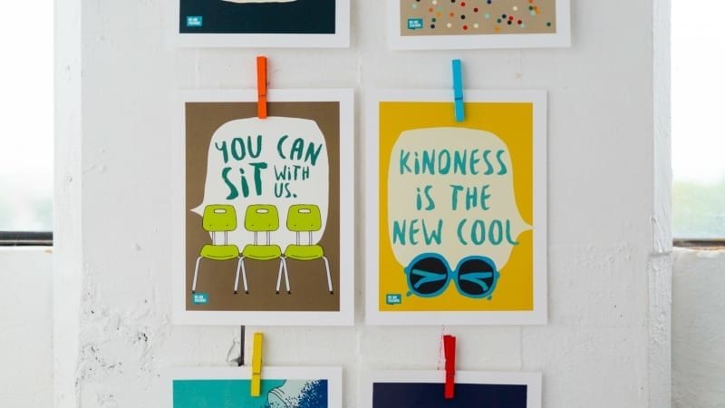 """Hanging posters that say """"You can sit with us"""" and """"kindness is the new cool"""""""