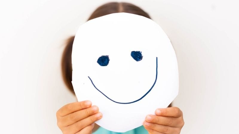 Girl holding hand-drawn smiling face in front of her face