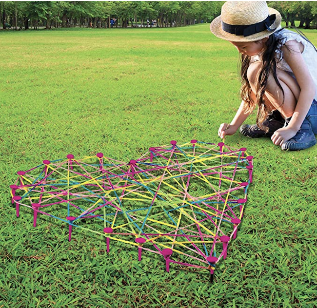 Girl creating lawn string art in her backyard, as an example of educational outdoor toys