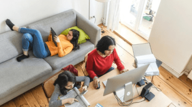 A woman working on her computer while a young girl sits next to her working and another girl lays on the couch with a tablet.
