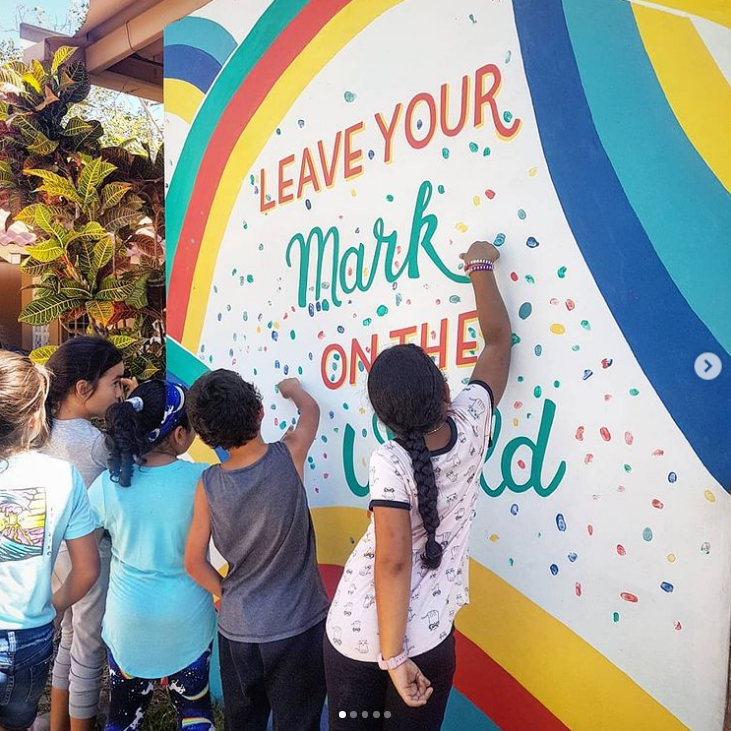 Students adding their fingerprints to a school mural