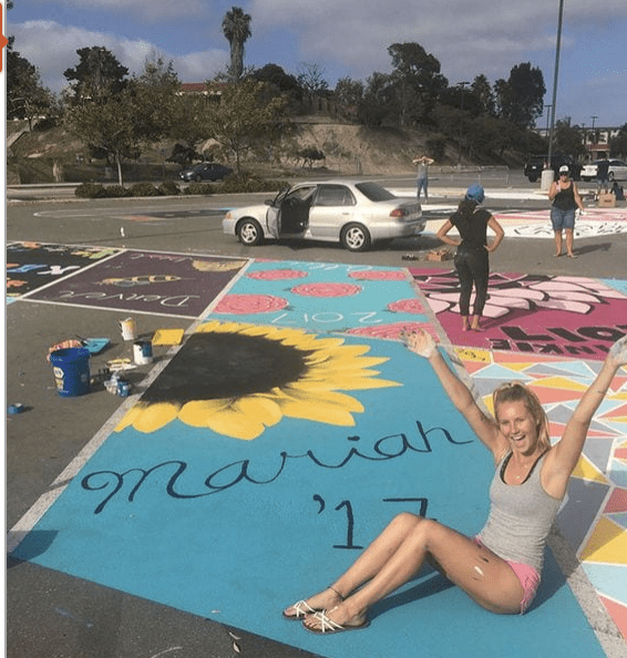 A picture of a high school senior siting in a parking spot she painted.