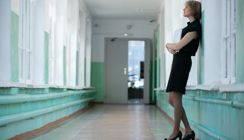 A Tired Teacher Standing in a School Hallway Learning on the Wall with Papers in her Hand