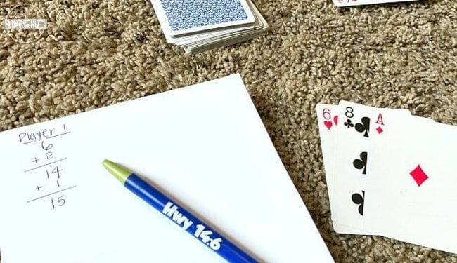 Playing cards with pen and paper on which is written a running total for Player 1