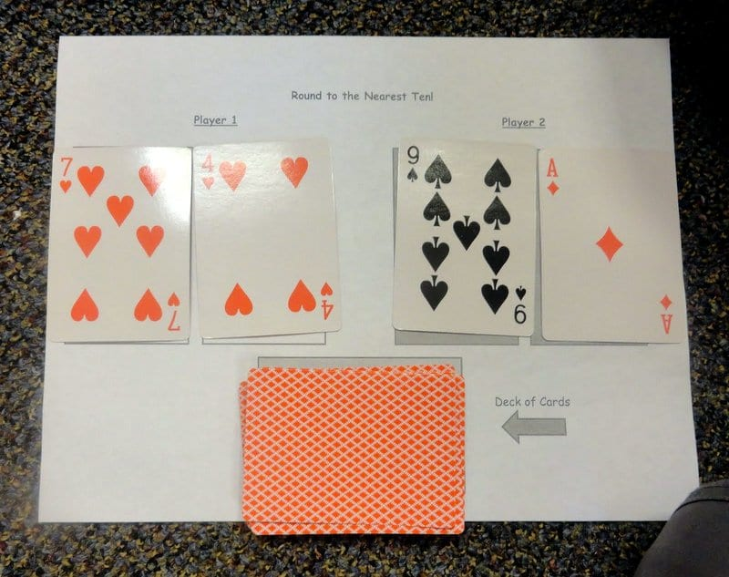 Playing cards laid out on printable worksheet called Round to the Nearest Ten (Math Card Games)