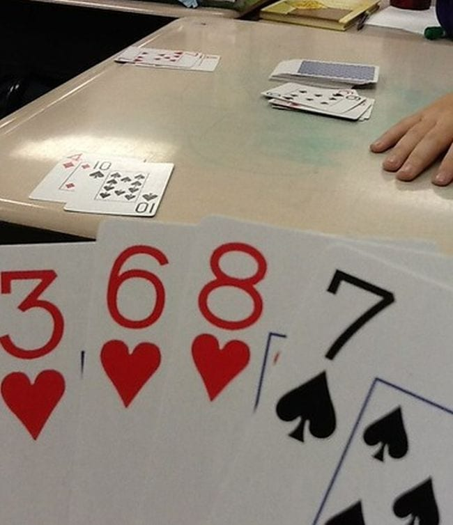 Student holding playing cards